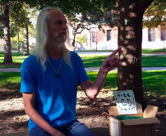 Local musician Gregg Brown visits Illinois State University's campus with a box of free CDs.