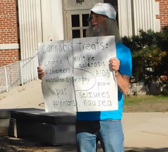 On the Illinois State University quad, Brown holds up a sign endorsing the use of cannabis as a medical treatment.