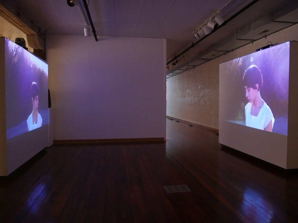 A two-channel video installation shows El Paso resident Aurore Tarango walking in the dry riverbed of the Rio Grande. Image courtesy of the artists.