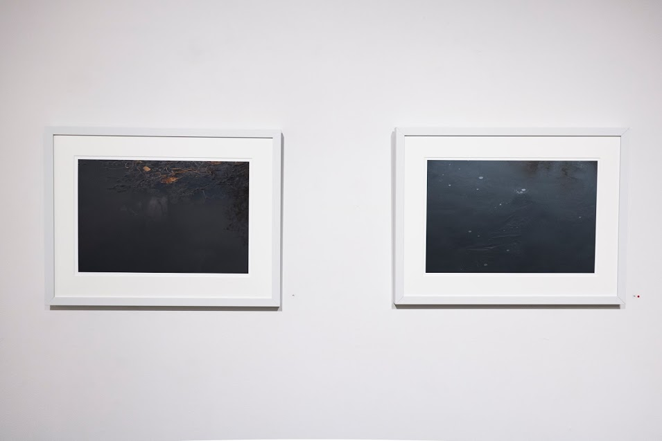 Nancy Fewkes,  Site A, Spring Lake, 11.15  and  Site A, Spring Lake, 1.17 , archival digital ink jet print. The image on the left depicts dark water with a greenish tint, marked by orange streaks toward the top. In the image on the right, the water is navy blue.Image courtesy of Lucas Stiegman.