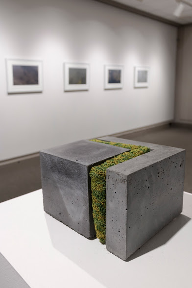 "Laura Primozic,  Microenvironments 1 , concrete, textile. A layer of green yarn woven into ""moss"" cuts an L-shape into a block of concrete. Image courtesy of Lucas Stiegman."
