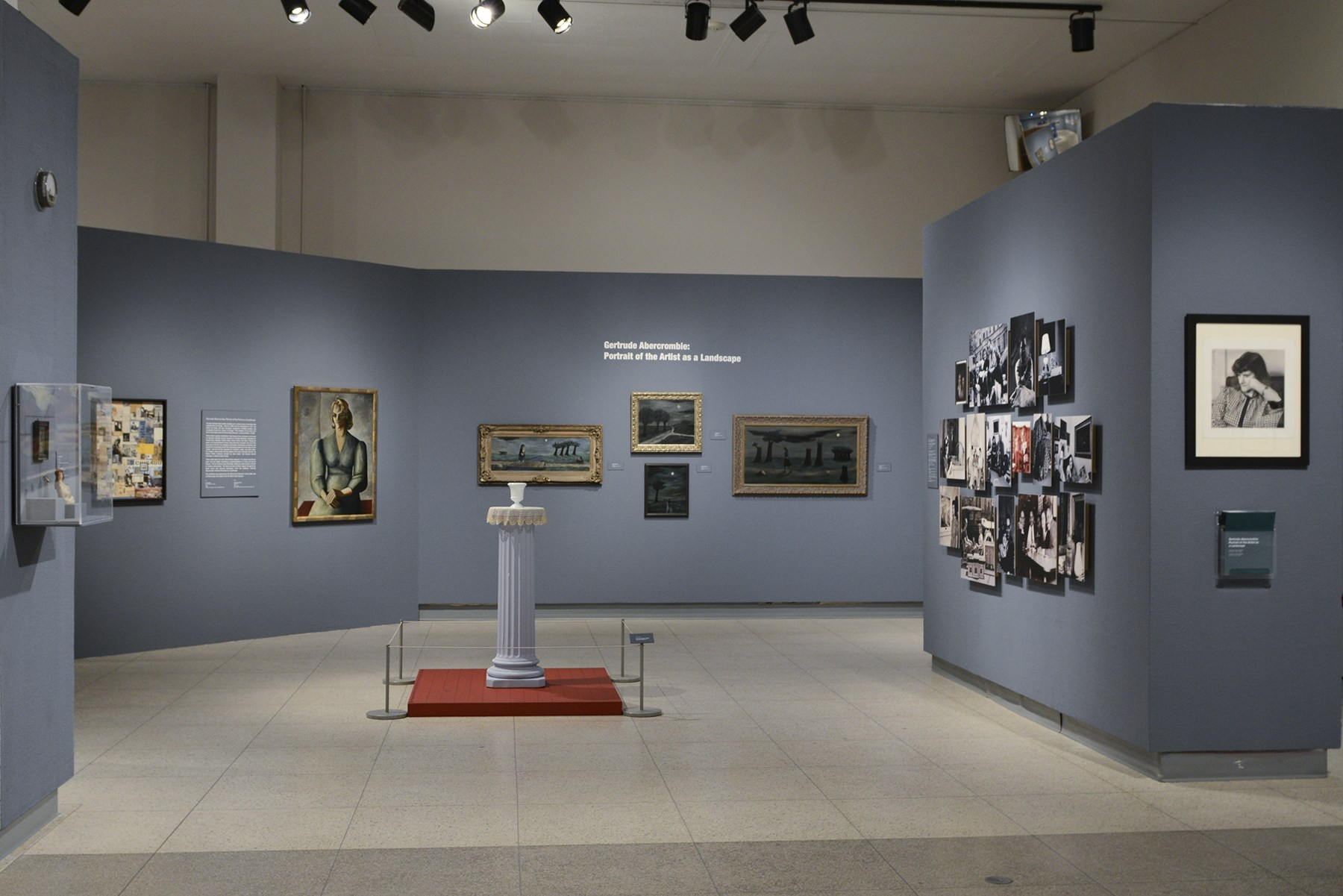 The entrance to the Abercrombie exhibition with dark gray-blue walls, a photo of her hangs to the right, on the back wall are several of her paintings and in the center is the still life display mentioned above. Image courtesy of the Illinois State Museum.