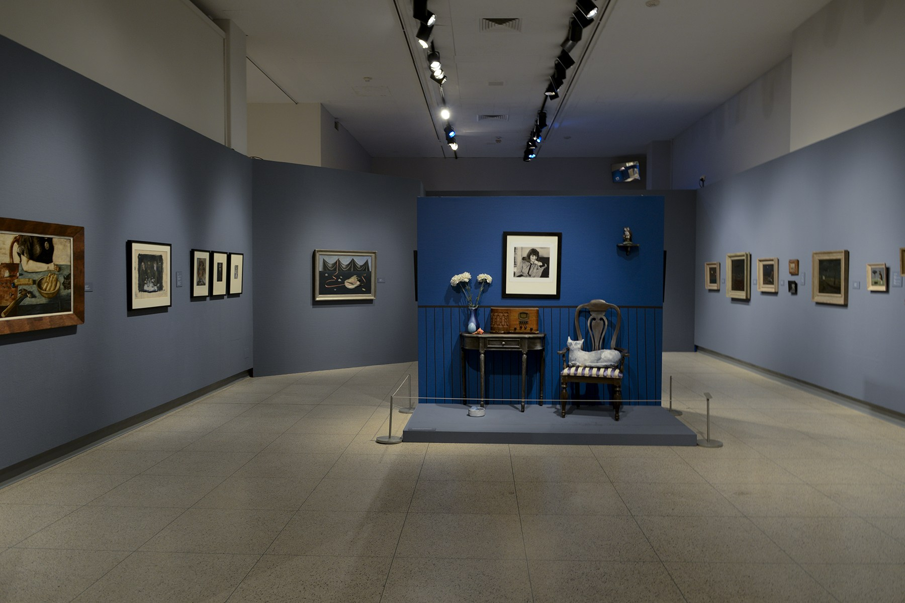 Looking through the exhibition there is a bright blue wall with a chair, cat, image of Abercrombie and a radio playing the music of Abercrombie's close friends Dizzy Gillespie, Sonny Rollins, and others. On the surrounding walls are many more works by Abercrombie. Image courtesy of the Illinois State Museum.