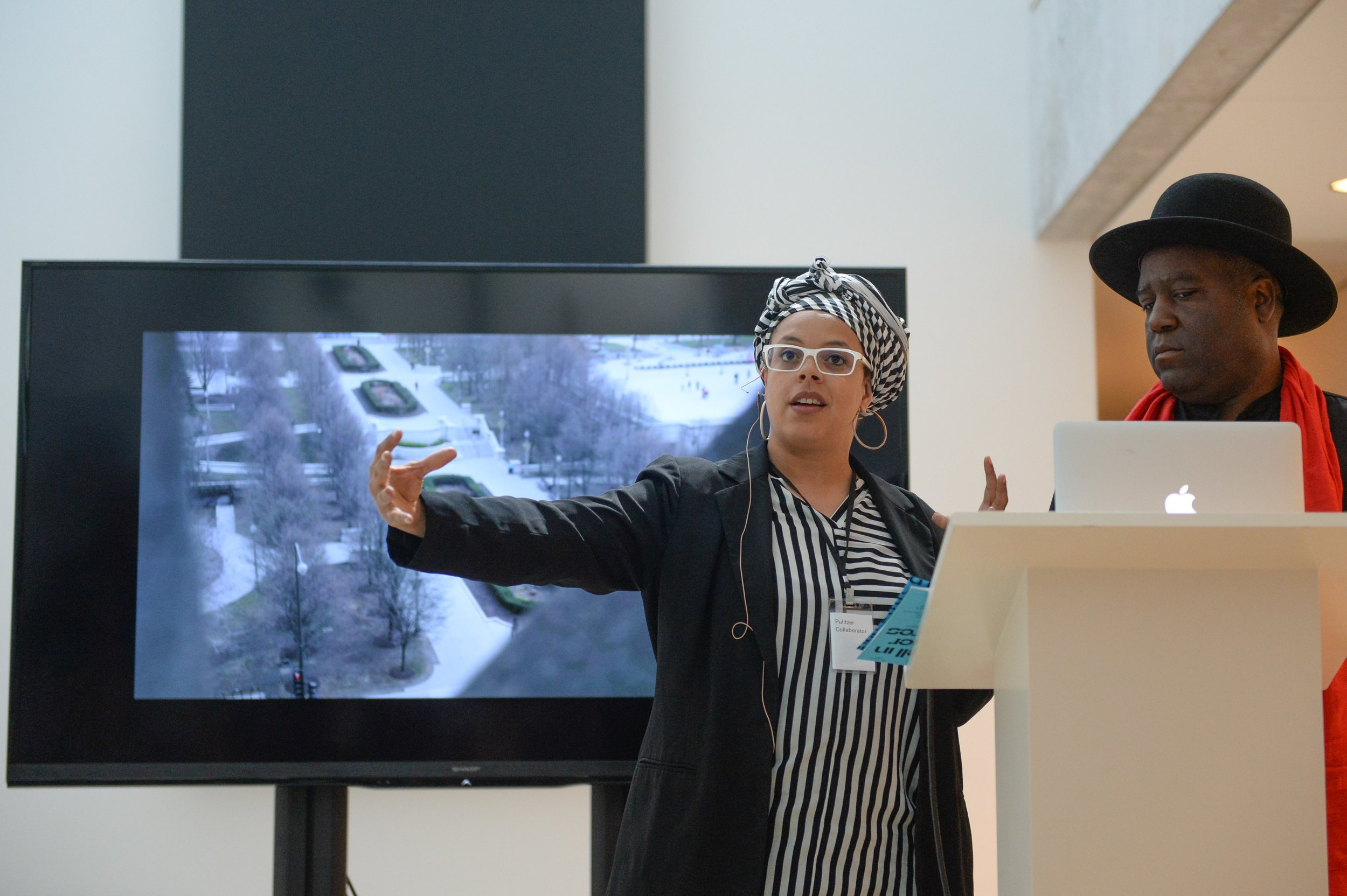 Mendi + Keith Obadike speaking in front of a screen at Dwell In Other Futures: Art / Urbanism / Midwest. Pulitzer Arts Foundation, St. Louis. April 28, 2018. Photo by Michael Thomas.