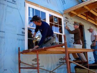 - Habitat volunteers installing energy efficient windows