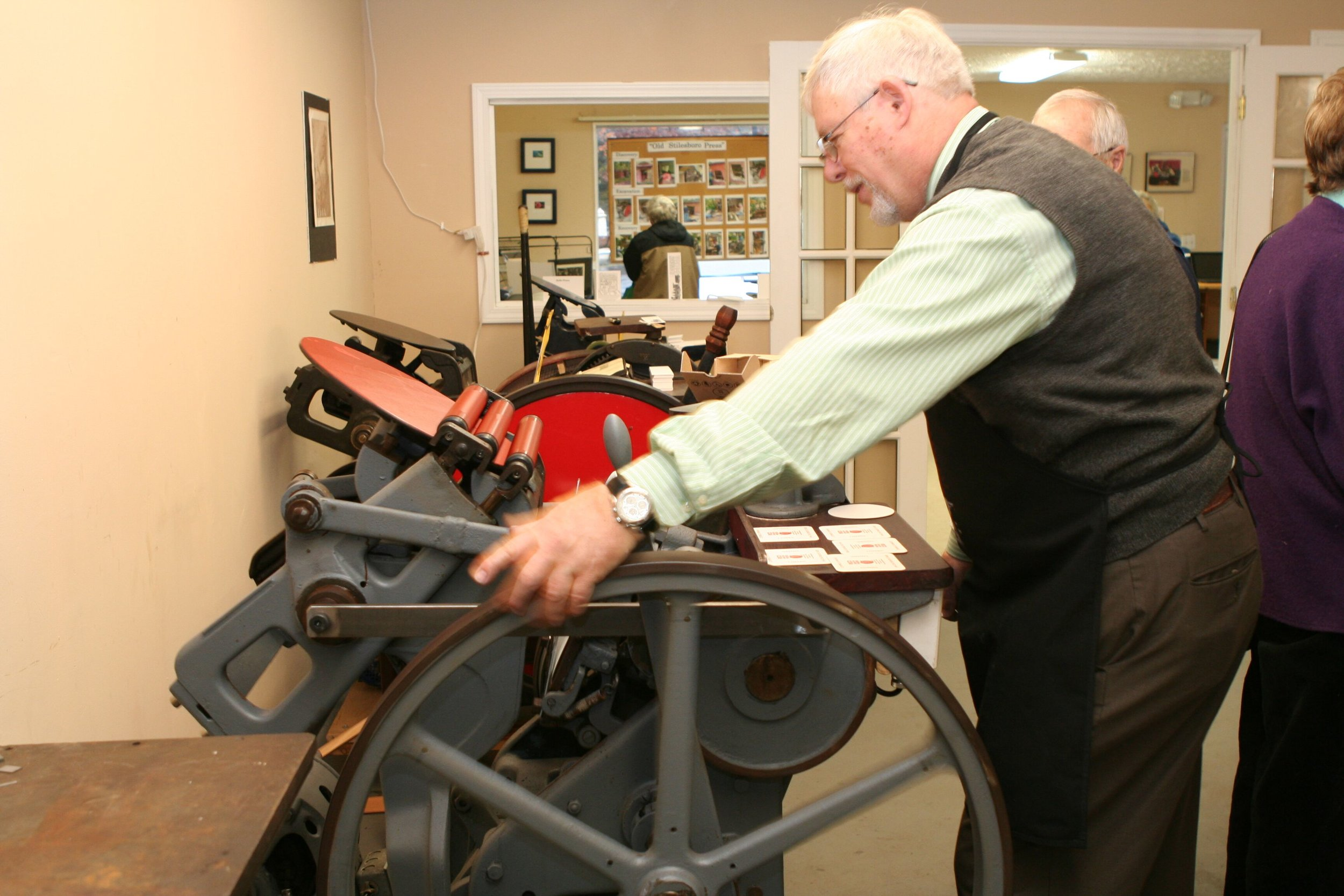 The weight of the press requires a push to get the flywheel to turn, allowing for the centrifugal force to maintain momentum.