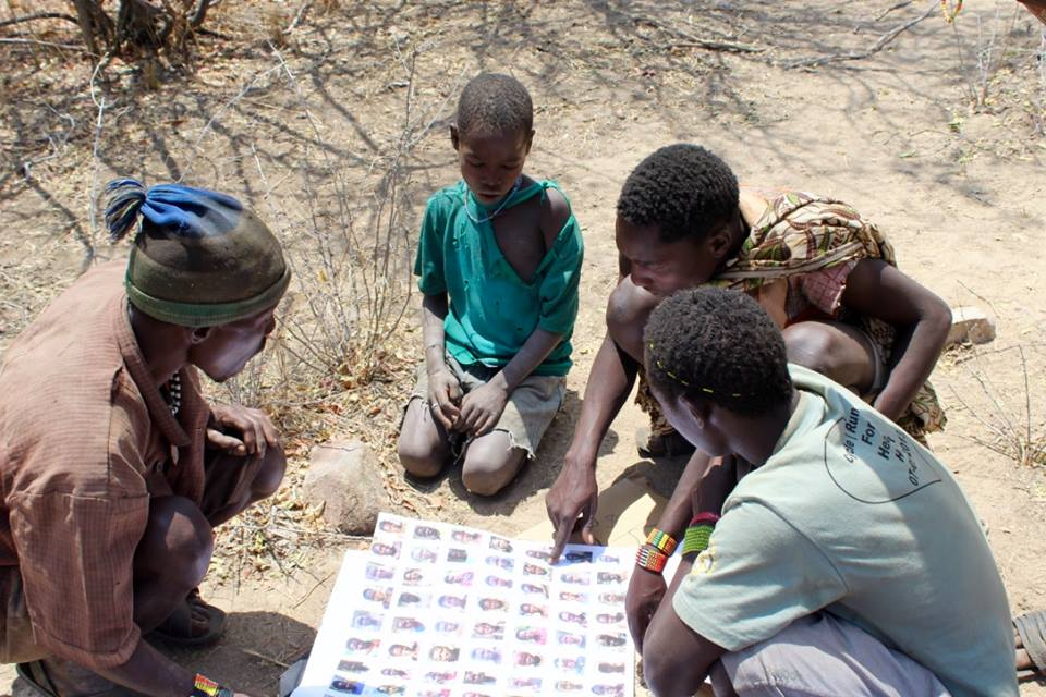 Hadza men looking through photos of other Hadza