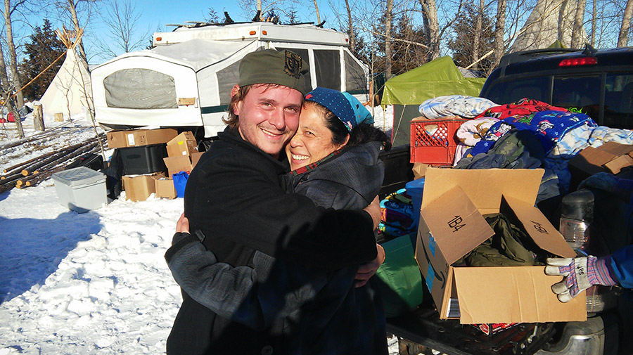 Frank and Leslie stop unpacking supplies at Rosebud Camp, anti-Dakota Access Pipeline protest, to show some mutual appreciation. Rosebud is part of the Standing Rock Sioux Indian Reservation in North Dakota, USA.