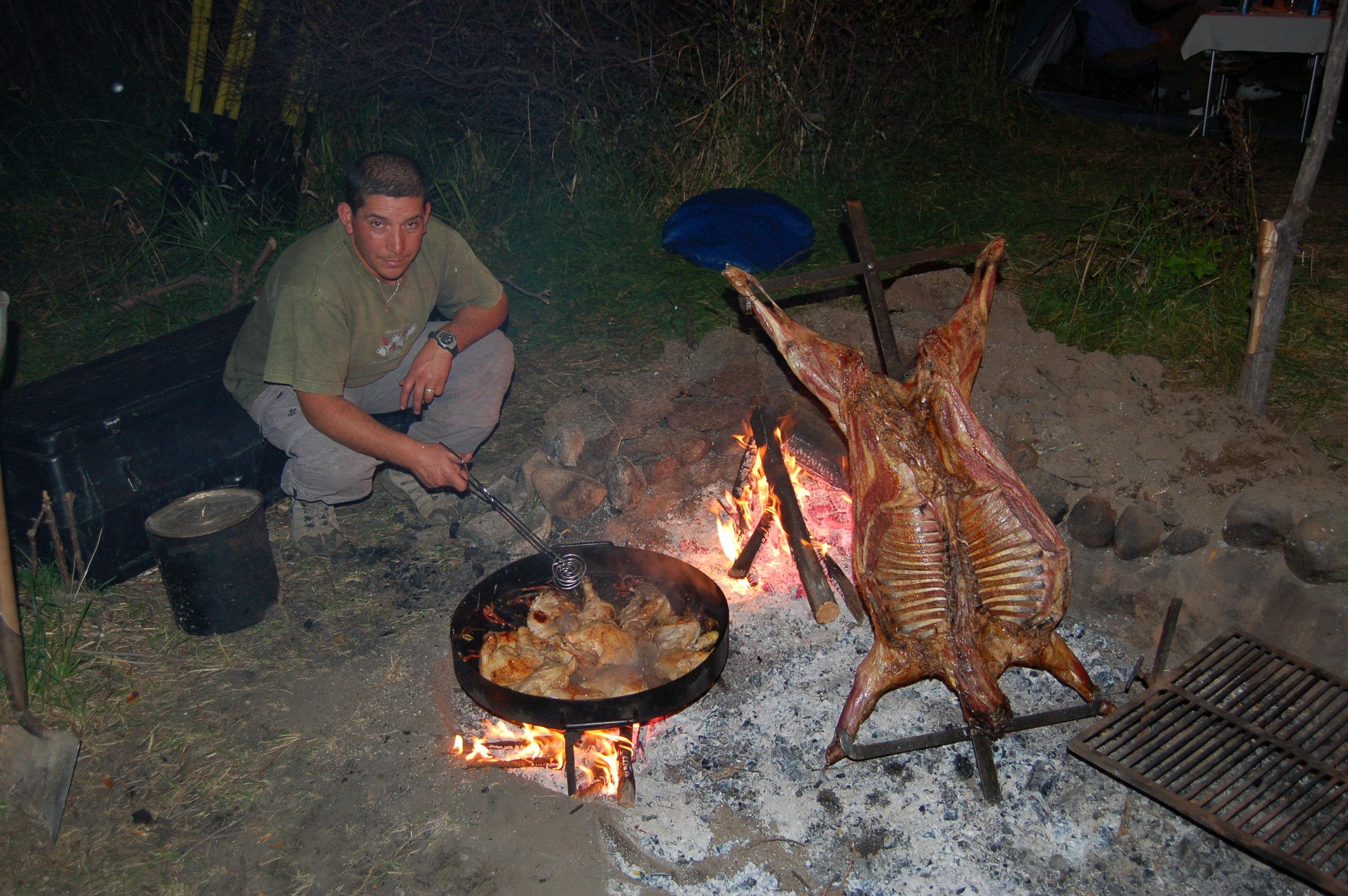 Preparing camp dinner at river side. Lamb a la cruza (on the cross) and pollo al disco (chicken seared on the disk). Fabulous!