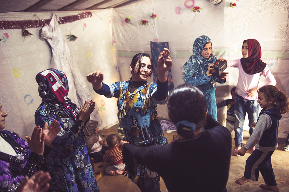 """Syrian refugees dance at a wedding celebration in a refugee camp in Marj El-Khokh, in Marjaayoun, Syria. The father of the groom said, """"We want to create life out of death .... People should not continue to be morbid."""" CREDIT: Lynsey Addario"""