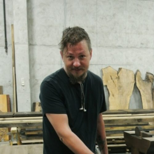 Ryan   Ryan, a Pratt Institute graduate, brings an artistic touch to the form and finishes of our tables. He has a great sense of color and is an artist in his own right. When he's not at the shop, he is at his own studio working on his paintings and woodcarvings.