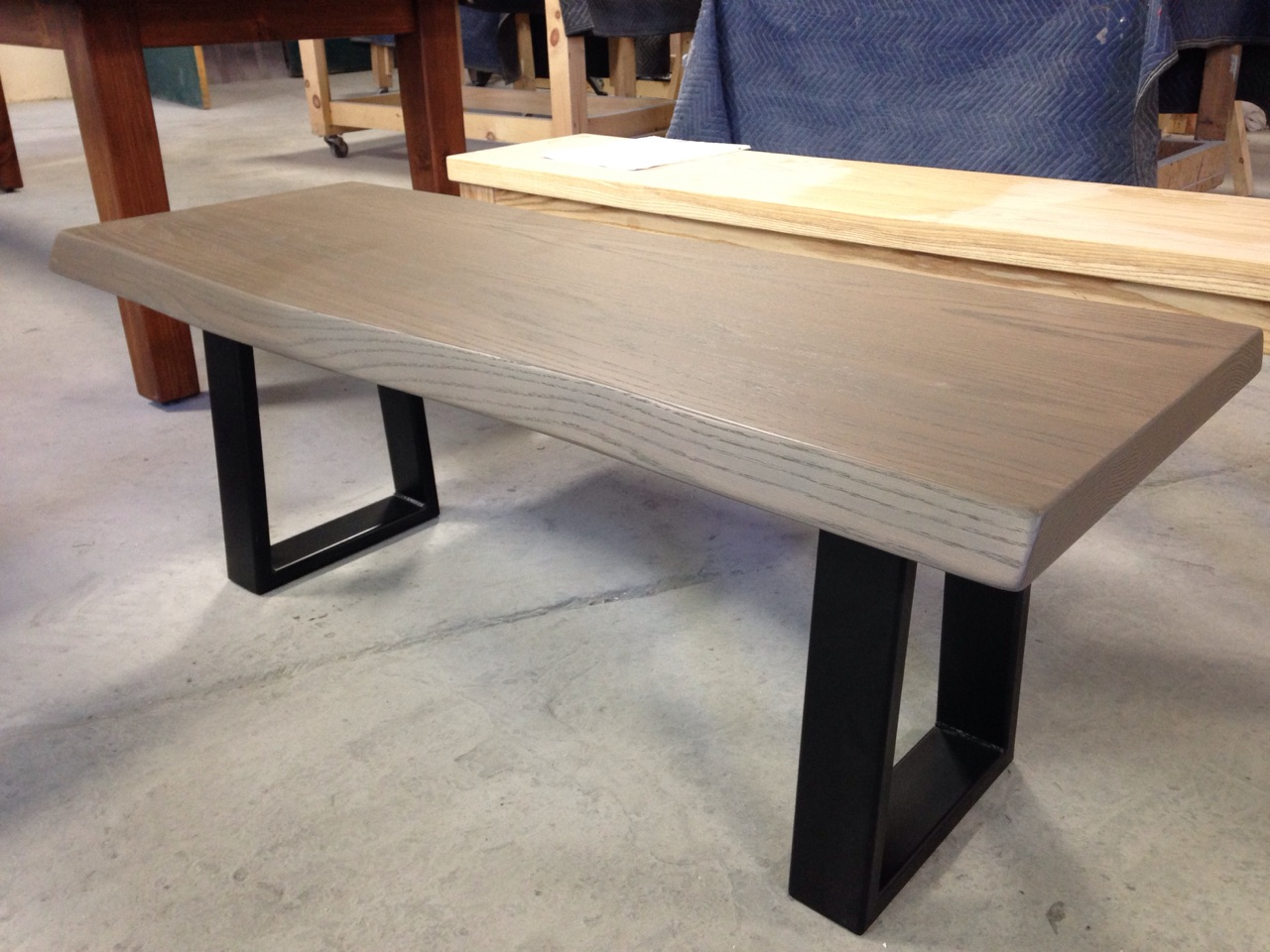 Ash Bench with a Subtle Live Edge and 3x1 Steel Legs in a Tapered Shape. Finished with a Light Wisteria Stain.