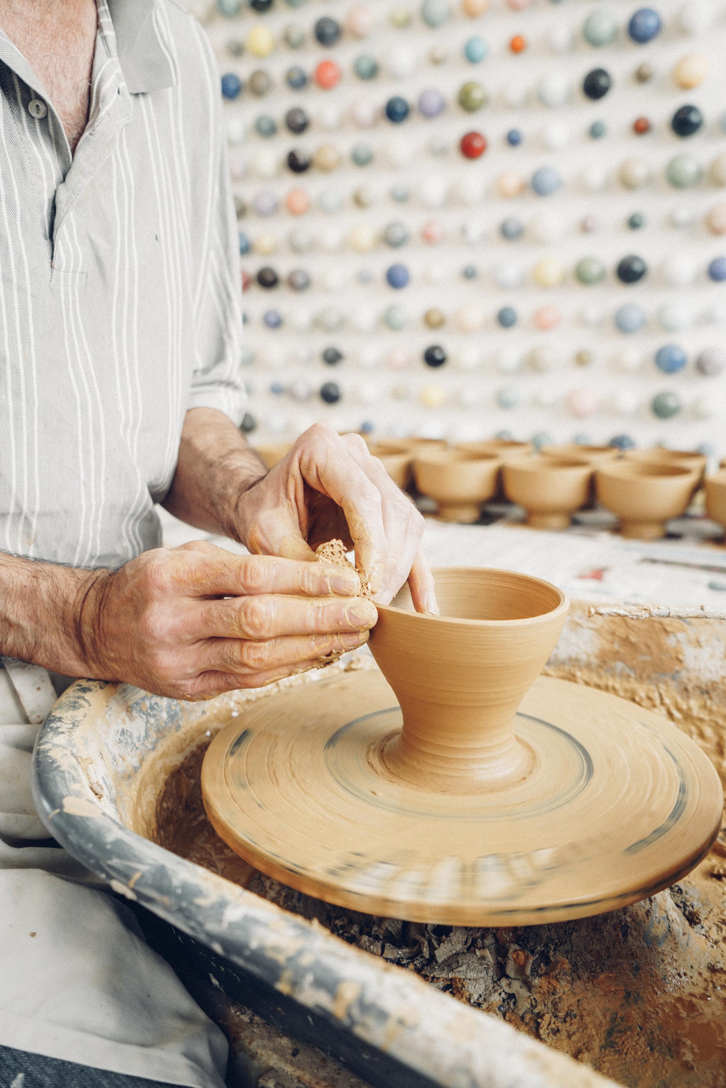 Studio Arhoj ceramist throwing a bowl