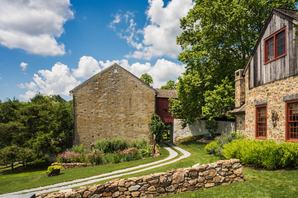 At this farmhouse, the use of stone walls and gravel roads divide up the property and areas of different types of gardens