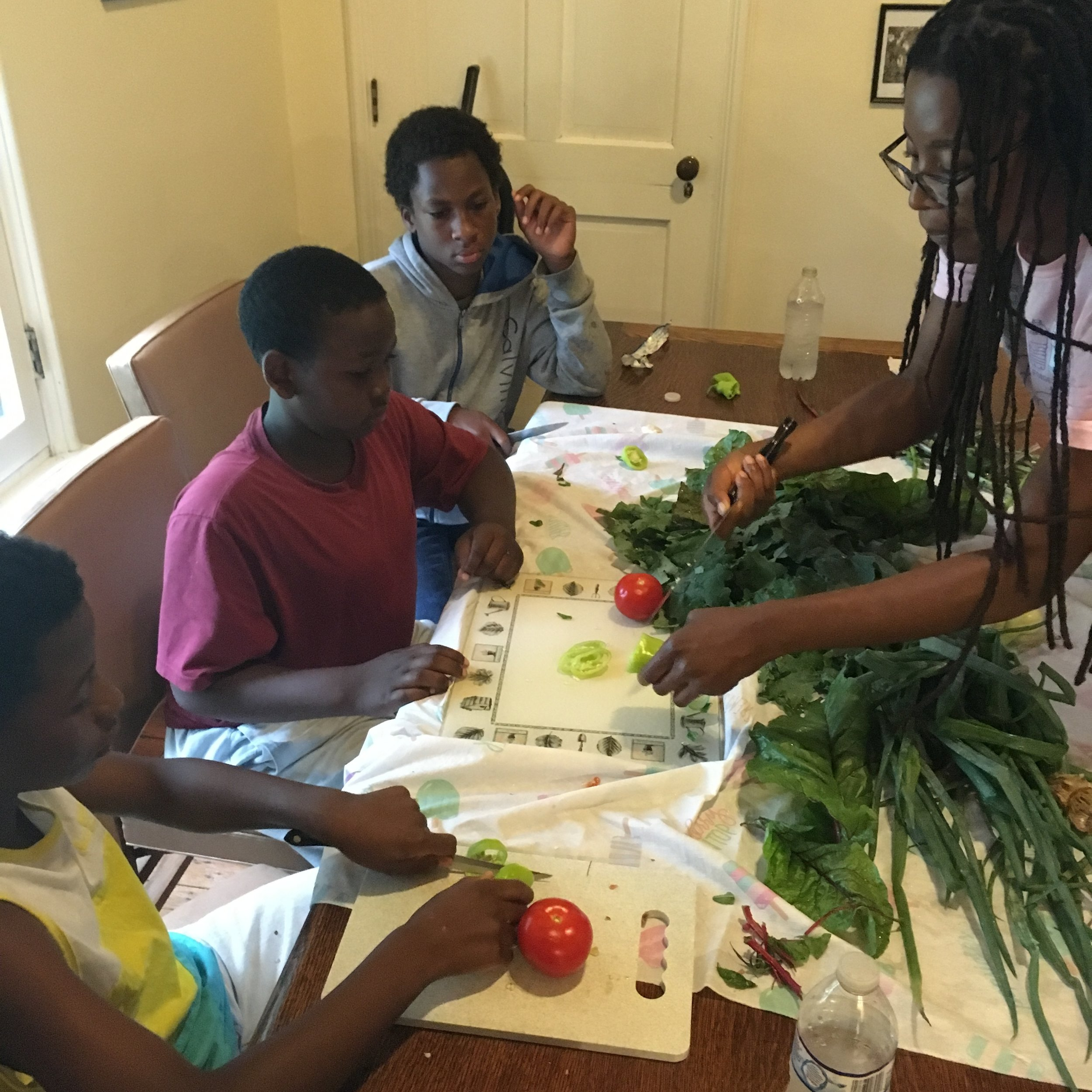 Christine helps some SEEDS participants get into some freshly harvested vegetables!