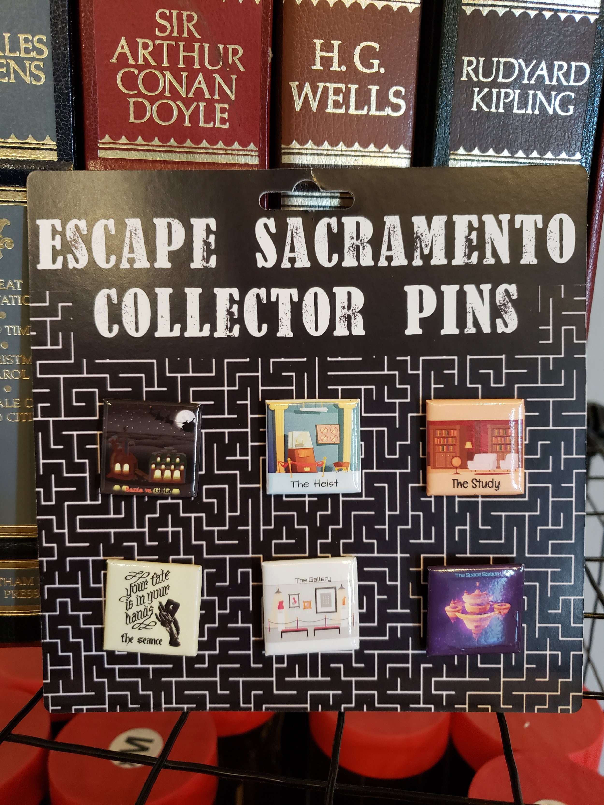 For our big reveal….DUN DUN DUN!!! This is our Escape Sacramento Collector Pin set. Each pin represents the games that we have debuted over time, here at Escape Sacramento. Santa vs. Gryla, The Heist, The Study, The Seance, The Gallery and The Space Station. $12