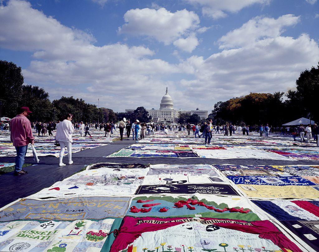 1987: A SPECTRUM OF RESPONSES - After learning that over 1,000 San Franciscans had died due to complications associated with AIDS, activist Cleve Jones created the first panel of the AIDS Memorial Quilt, a tribute that would grow to cover the entirety of the National Mall in Washington. In the same year, academic Debra Fraser-Howze founded the National Black Leadership Commission on AIDS. Activists worked against a landslide of public fear and apathy in AIDS' early days, and U.S. immigration even banned people who were HIV+ from entering the country — a decision that lasted until 2009.In the wake of this anxiety, England's Princess Diana famously took a different path by shaking the hand of an HIV+ man, without wearing gloves. Publicly challenging the misconception that HIV/AIDS was transferred by touch, Princess Diana demonstrated in a single gesture that the correct response to people living with HIV was compassion, not fear and ignorance.By the end of the decade, the World Health Organization estimated that there were 400,000 cases of AIDS worldwide.