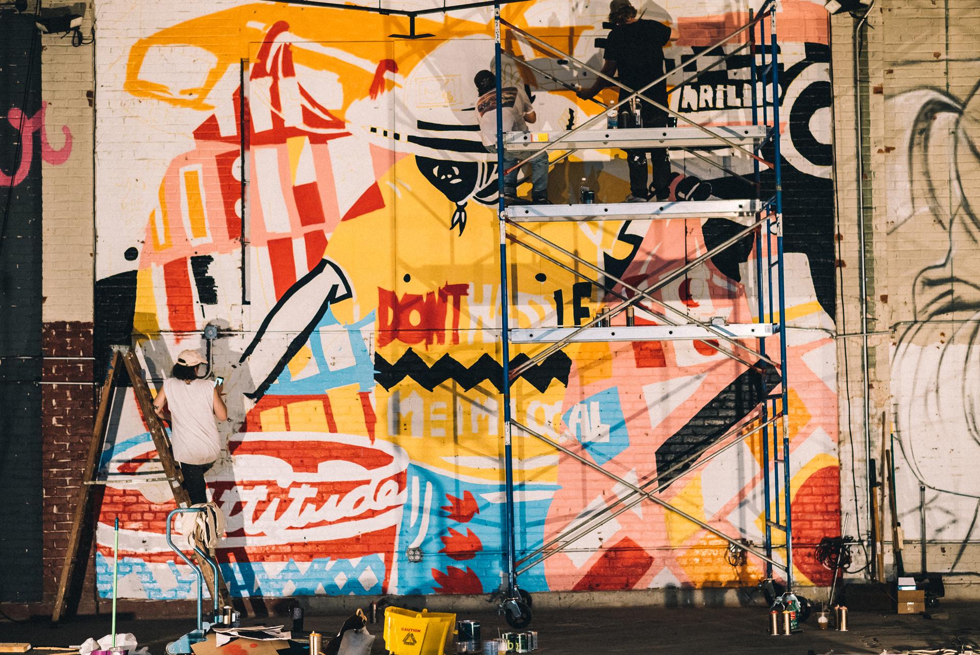 "Adam Lucas working on ""Don't Hassle Me"" mural, Market Surplus, June 2017"