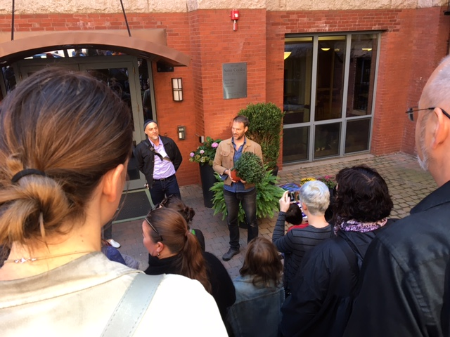 [Image: a group gathers to listen to two men discuss the edibility and uses of plants. One is holding a potted mum. In the background is a red building and sunken courtyard.]