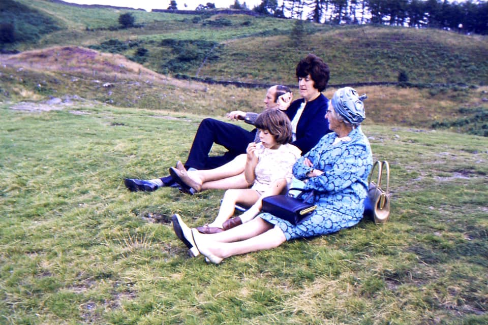 Rachel Kirk – Near Tarn Hows 1969ish. Mum & Nanny are sporting a lower heel for hiking, Dad in sports jacket & tie. I have a broken arm under my tee shirt and a gob full of Kendal Mint Cake. Nanny is rocking the jaunty hat/handbag combo. Amazing to think what I wear/carry as essential for a hike these days. We'd walked miles dressed like that!