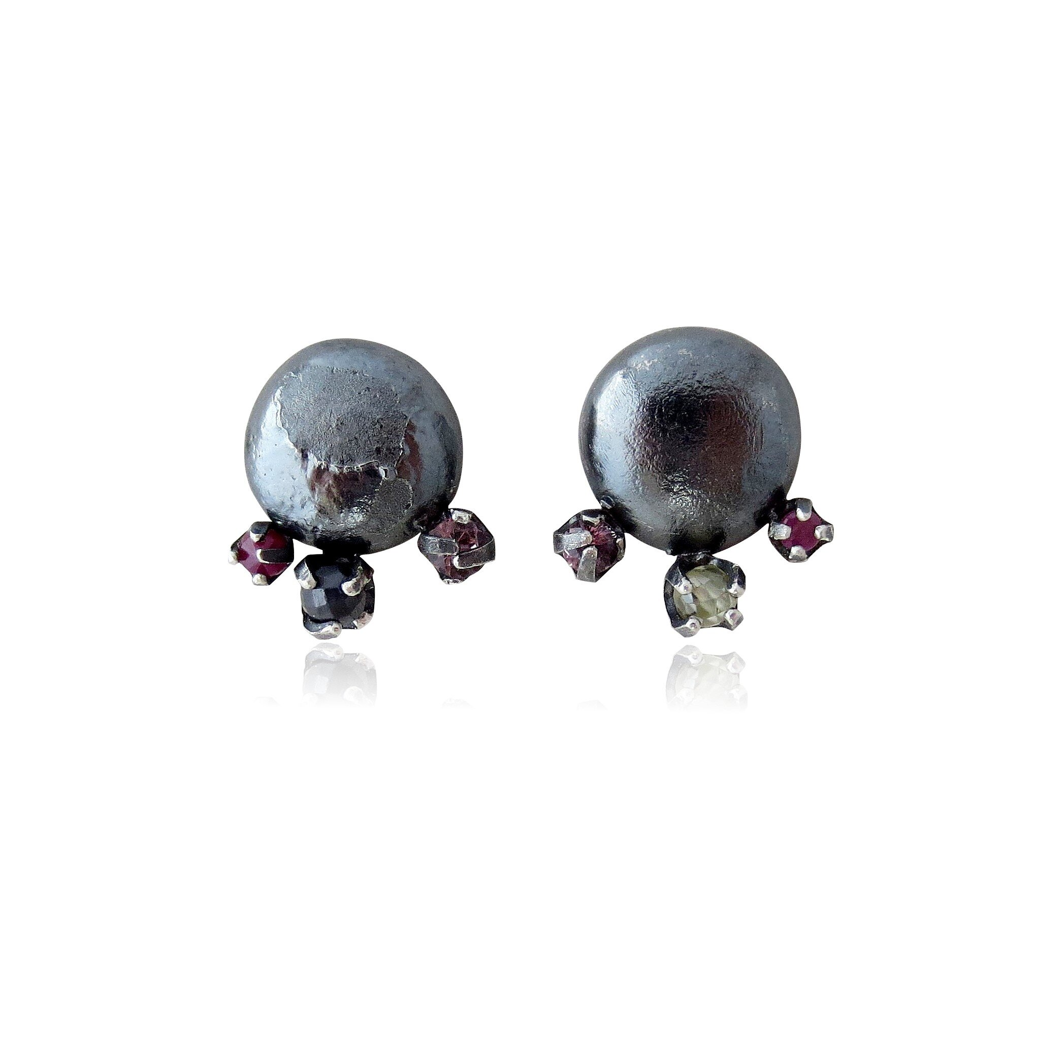 Oxidized sterling silver with cubic zirconia, pink sapphire, and rubies.