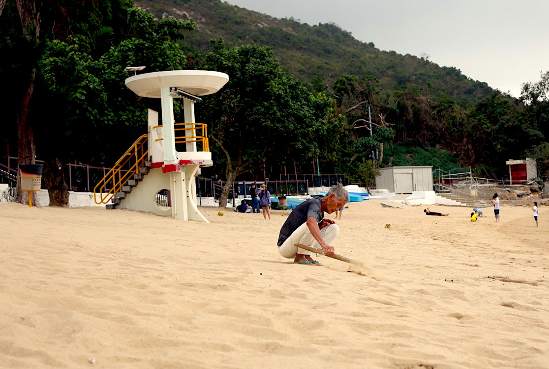A man spends hours sweeping this beach on Llama Island, Hong Kong. Photo courtesy:  Kuba Wasowicz .