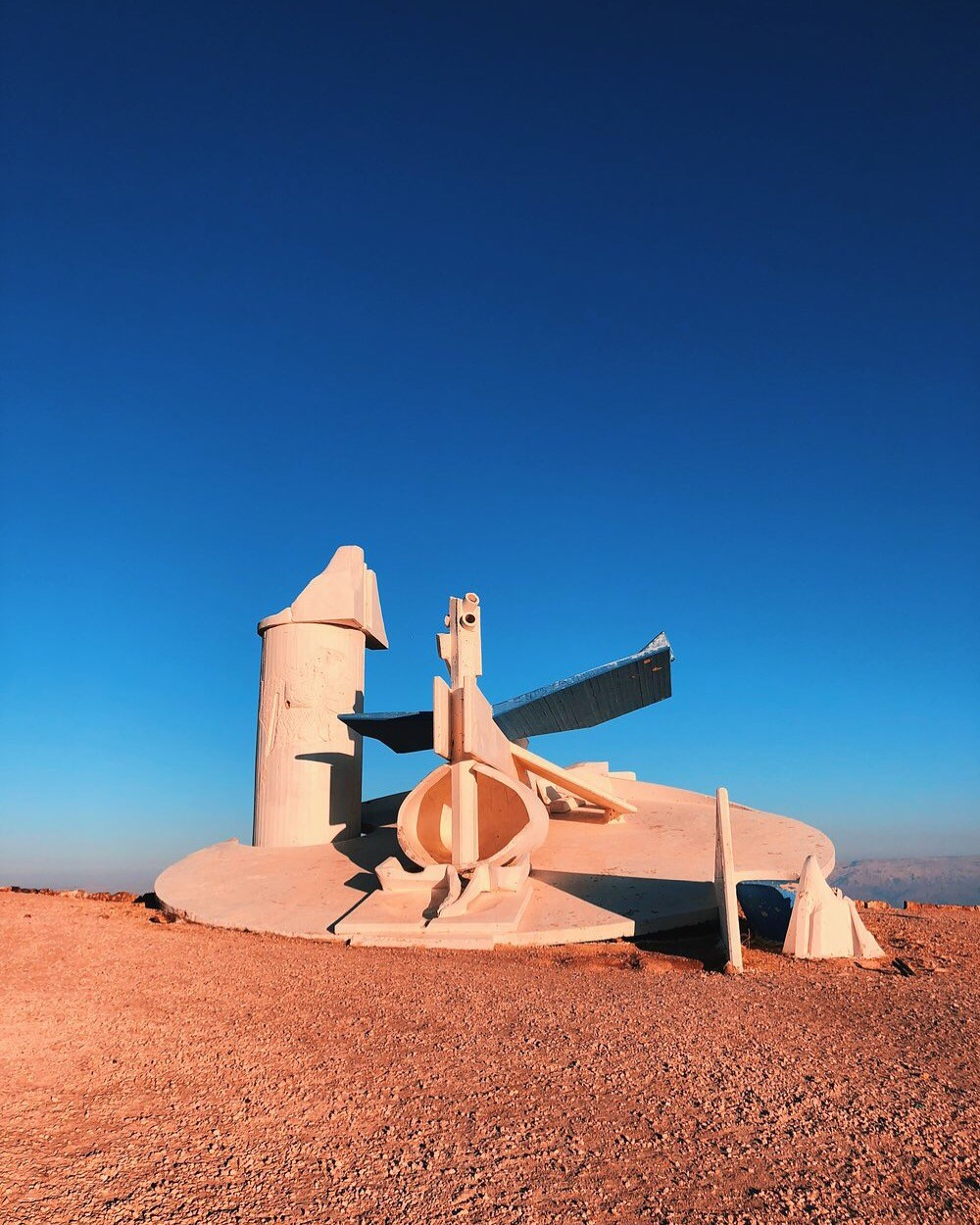 a modern statue sits in the middle of the Negev Desert