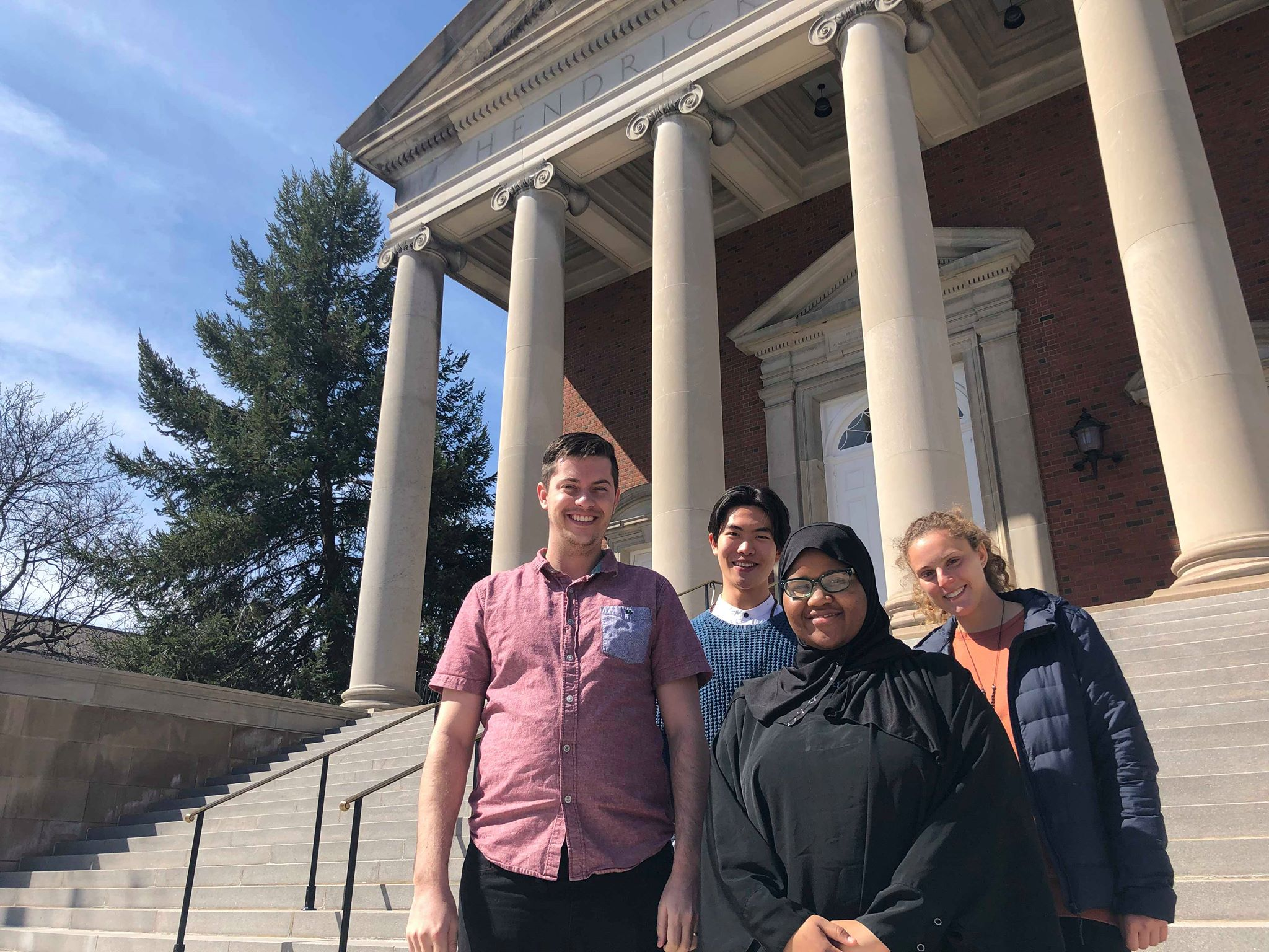 Four members of the Student Assembly of Interfaith Leaders, Dallin Evans, Junjie Ren, Dahabo Farah, and Haley Sussman (left to right), stand in front of Hendricks Chapel. Photo Courtesy: Hendricks Chapel
