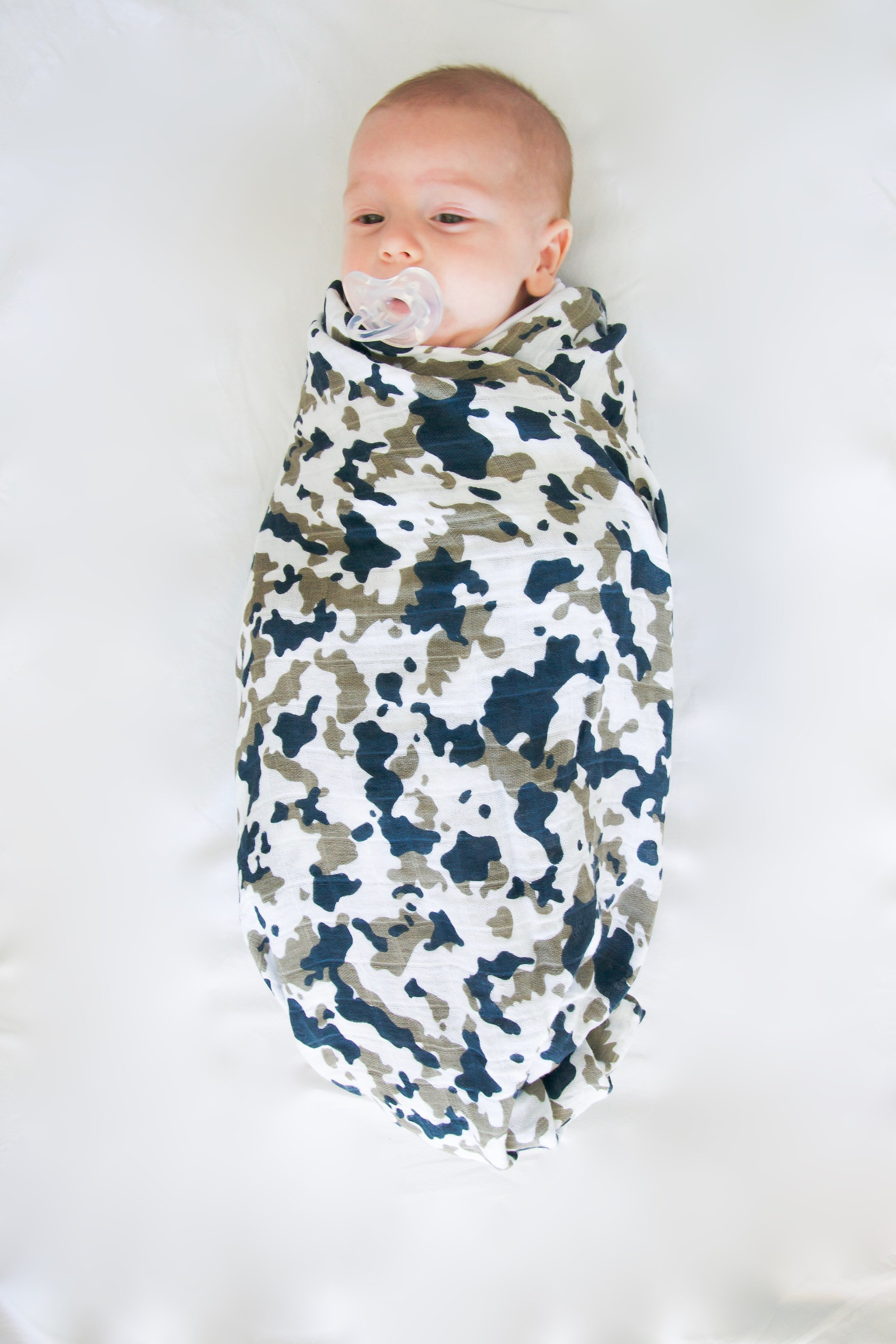 Here's our friends baby swaddled in our  Camo Cotton Muslin Swaddle