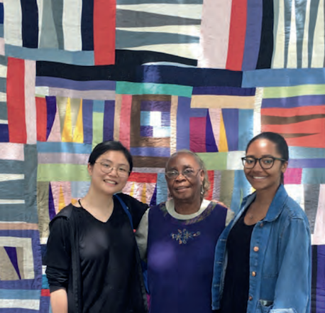 Luo '19 and Williams '19 with Mary Lee Bendolph, in front of one of Bendolph's quilts. Photo by Rubin Bendolph Jr.
