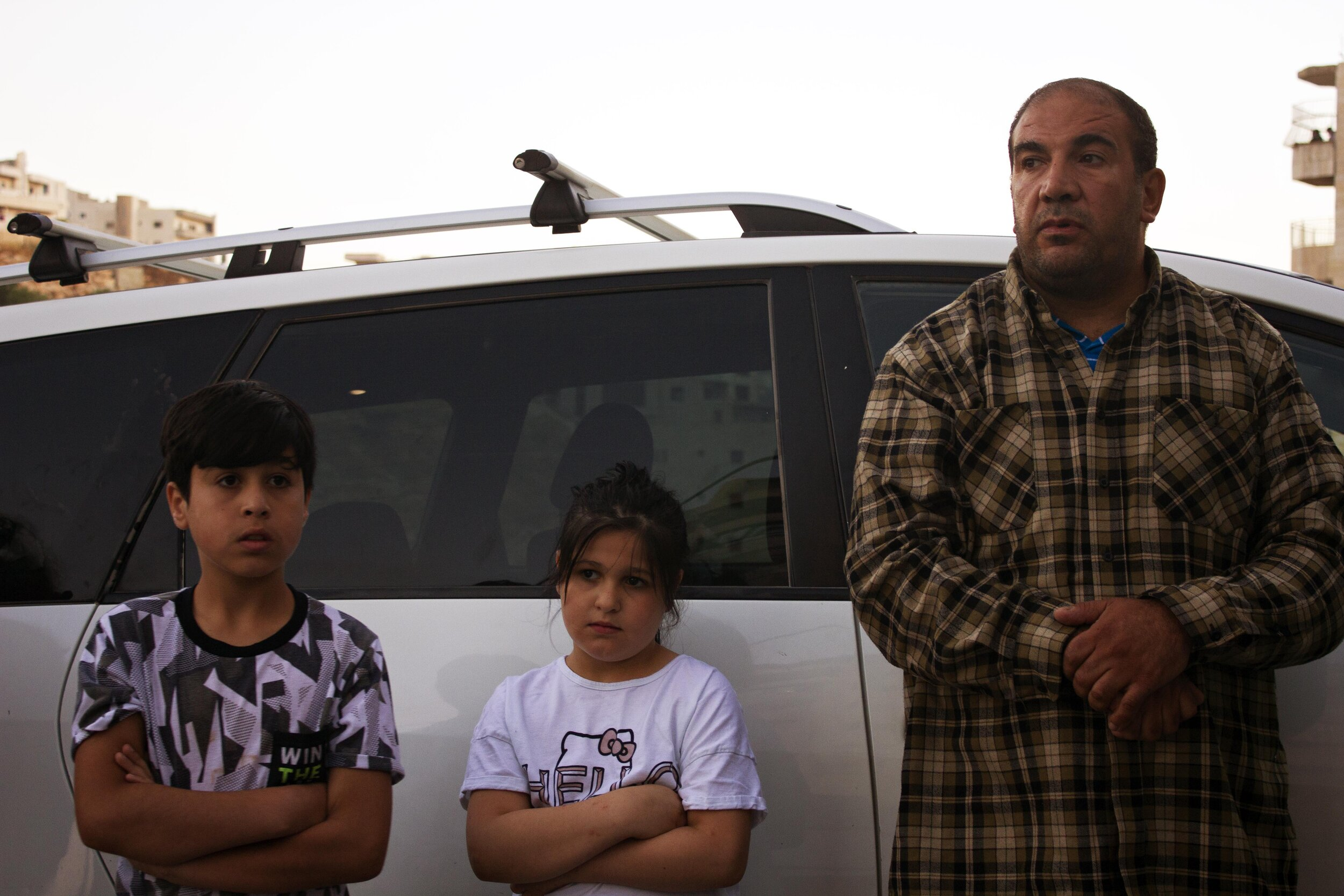 Two children and their father watch as soldiers prepare to demolish their home.