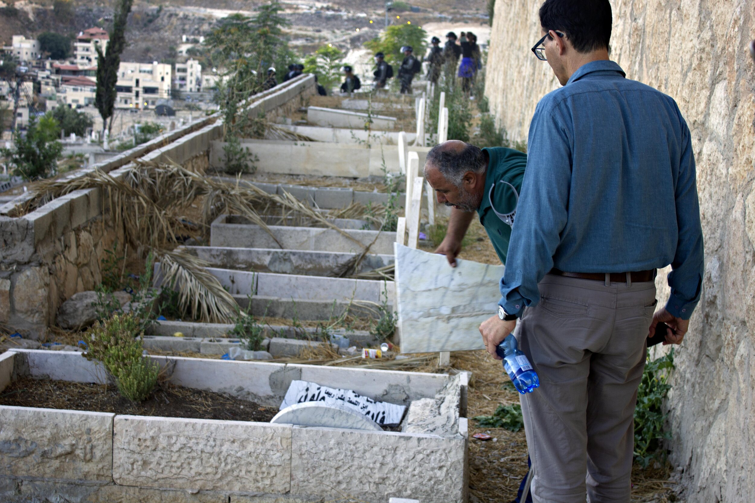 Mohammad Abu Hummus picking up the pieces of a gravestone that an Israeli police officer smashed