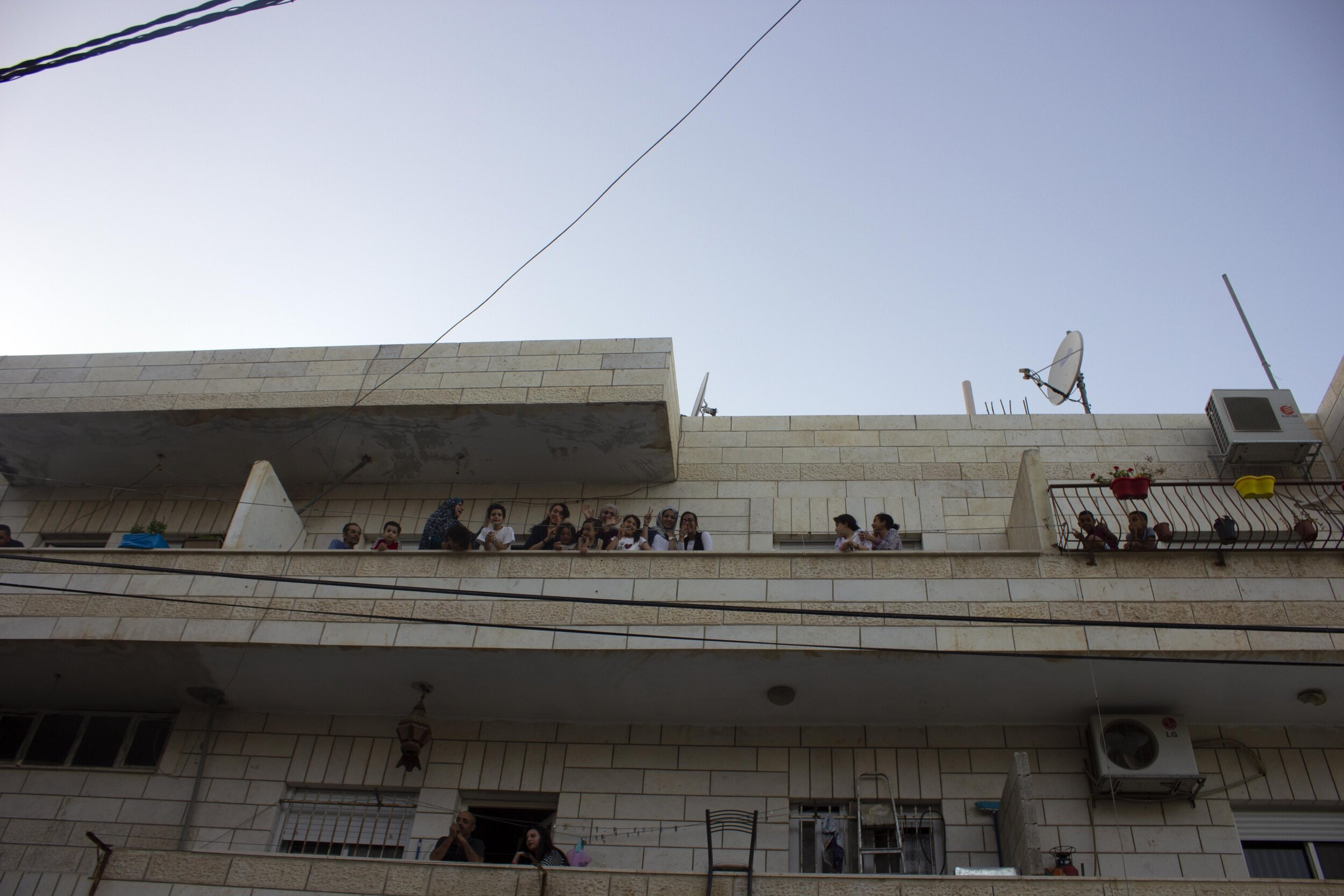 Children gather on a balcony to cheer at activists