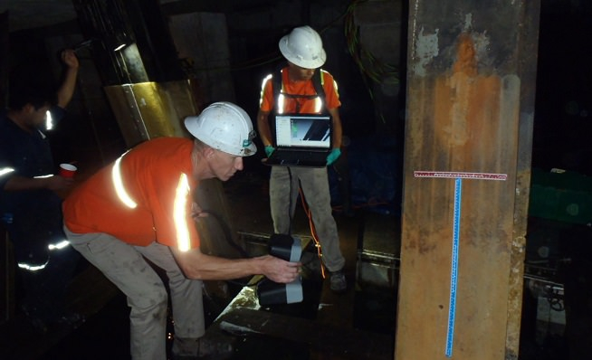 Technicians using a photogrammetric scanner to assess section loss of piles