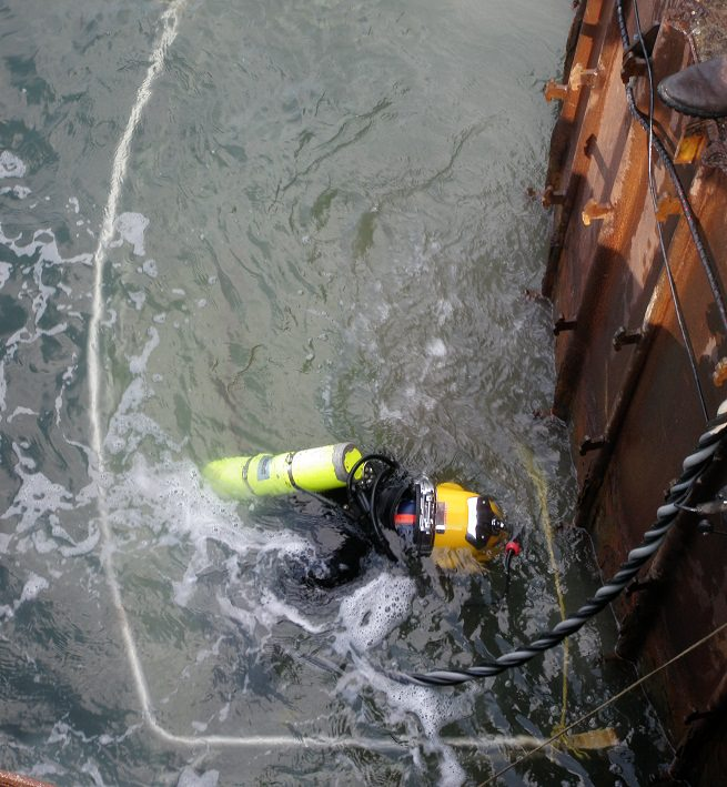 Commercial diver hydroblasting surface prior to placeing steel