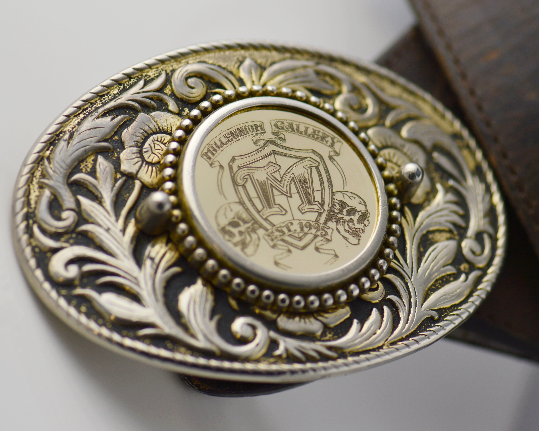 A vintage belt buckle modified to carry a custom engraved solid gold coin with the shop logo for a staff gift.