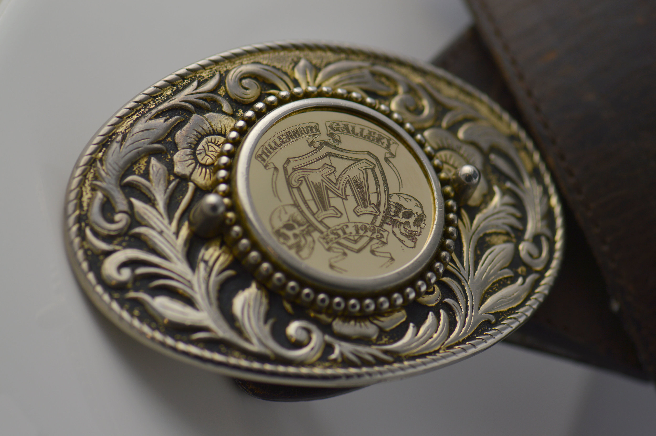 Engraved 1 ounce gold coin in a vintage belt buckle celebrating 10 years with the company.