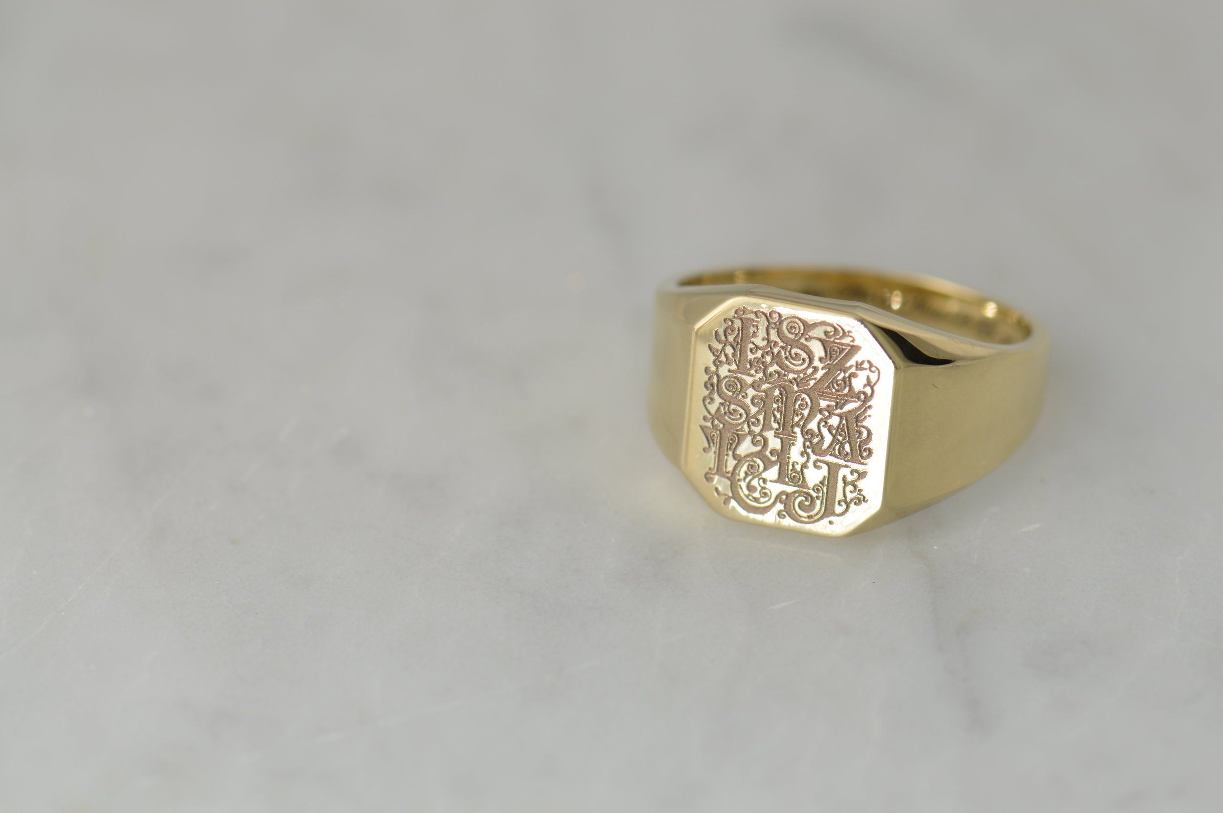Hand drawn family engraving on a gold signet ring.