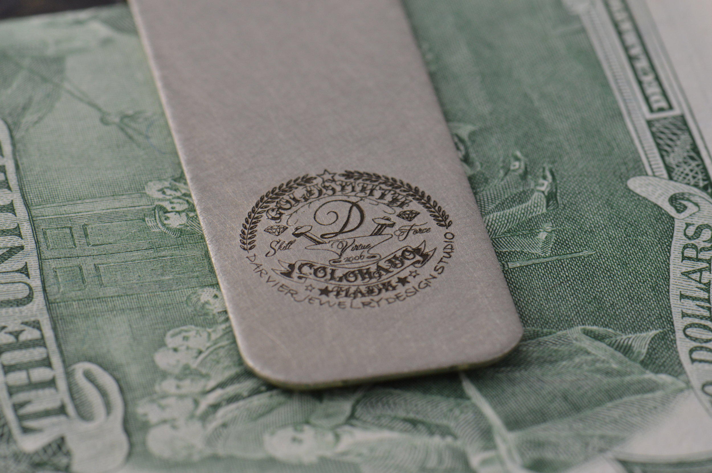 Darvier tattoo logo on a steel money clip illustrating a gift idea in our showroom.