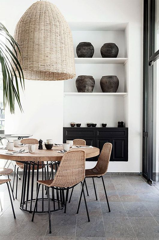 A beautiful dining space incorporating black, rattan, and a light toned pendant. Warms up the space, right? (Image: modernchairs.eu)