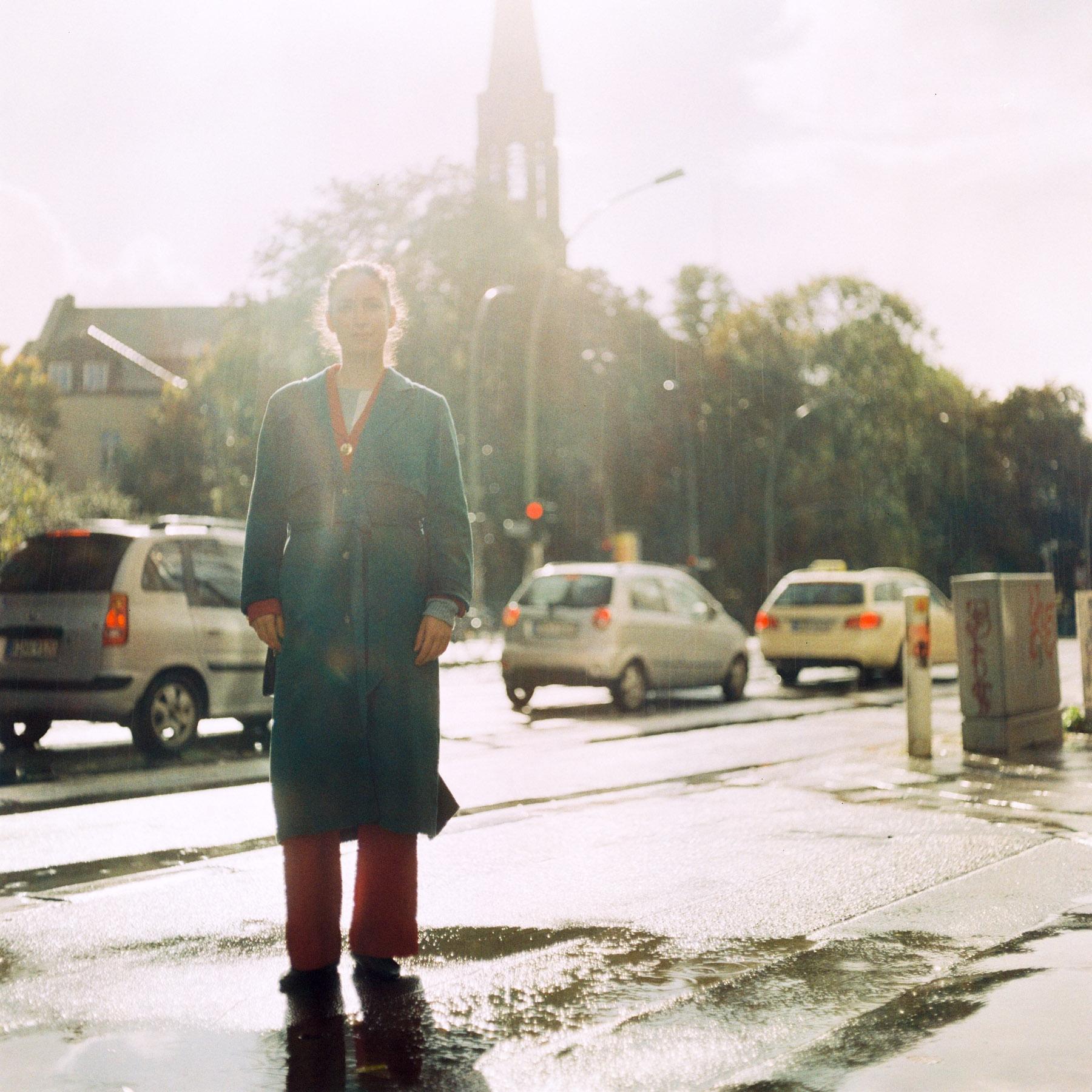 Jenya trägt einen grünen Mantel und roten Designer Anzug im Regen - Berlin.