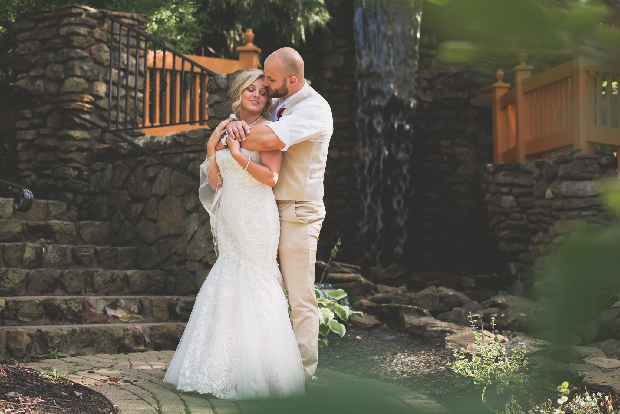Bride and Groom hugging by waterfall at Landoll's Mohican Castle.