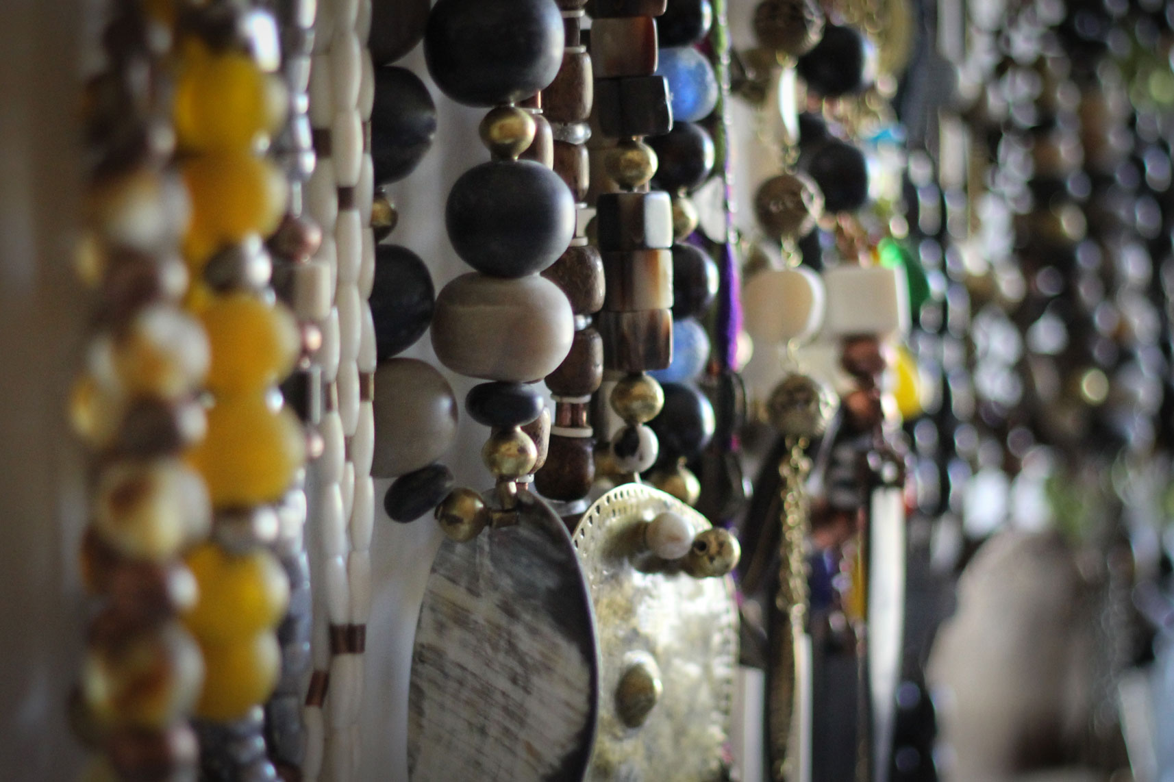 Selection of glass, horn and bone beads and bronze pendants