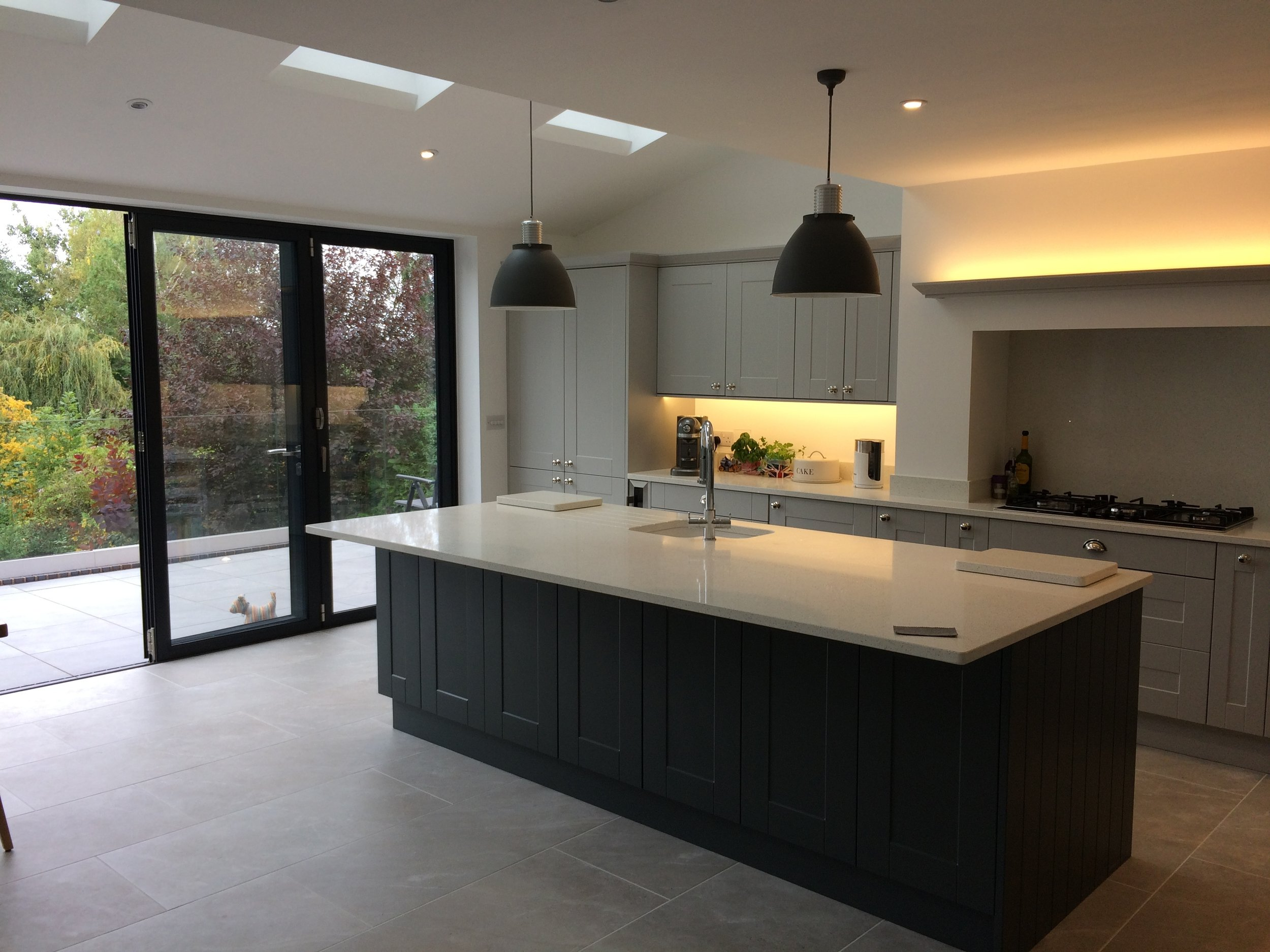 large bi-fold doors emphasis the kitchen's elevated position amongst the trees