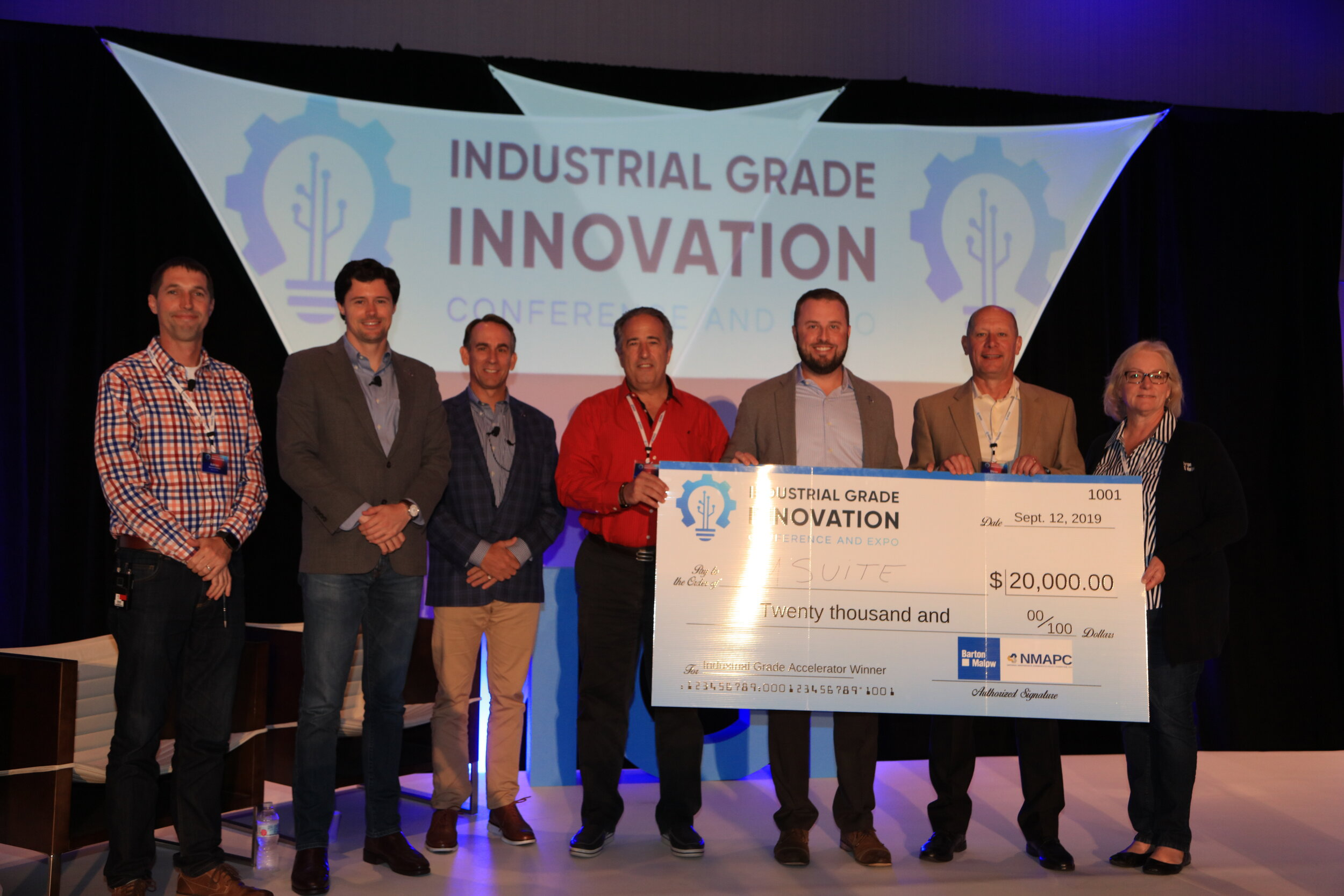 Britton Langdon (third from right), President of MSuite, accepts the winner's check.