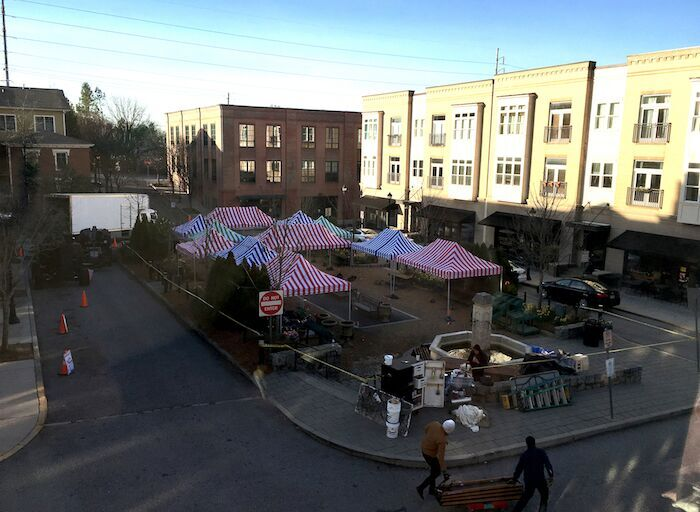 BEGINNING TO CREATE THE MARKET, STARTING WITH BRIGHT STRIPED TENTS.