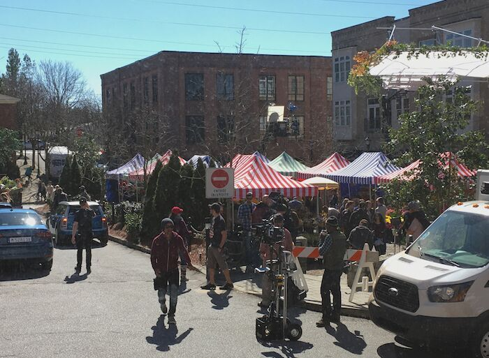 THE 200+ EXTRAS ARE IN PLACE, SHOPPING AT THE MARKET WHILE SCENES ARE FILMED.