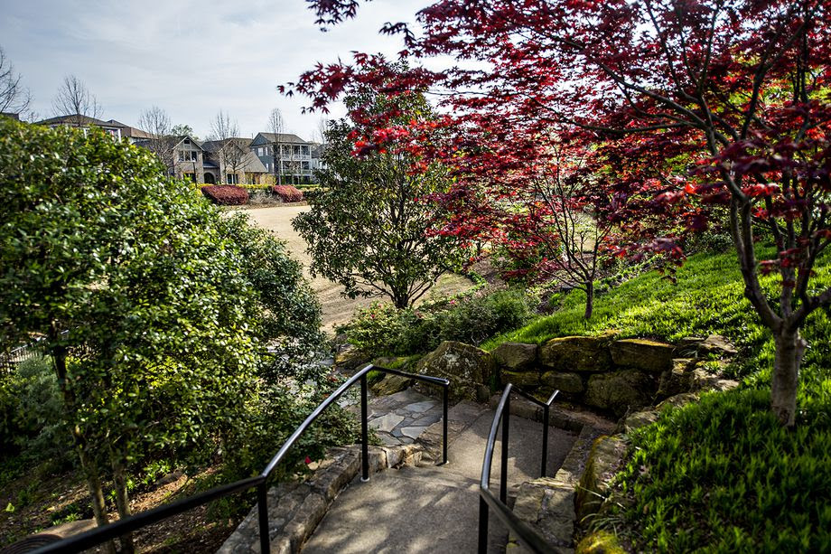 Rich landscaping wraps Brewer Park, the community's central green space ideal for congregating.