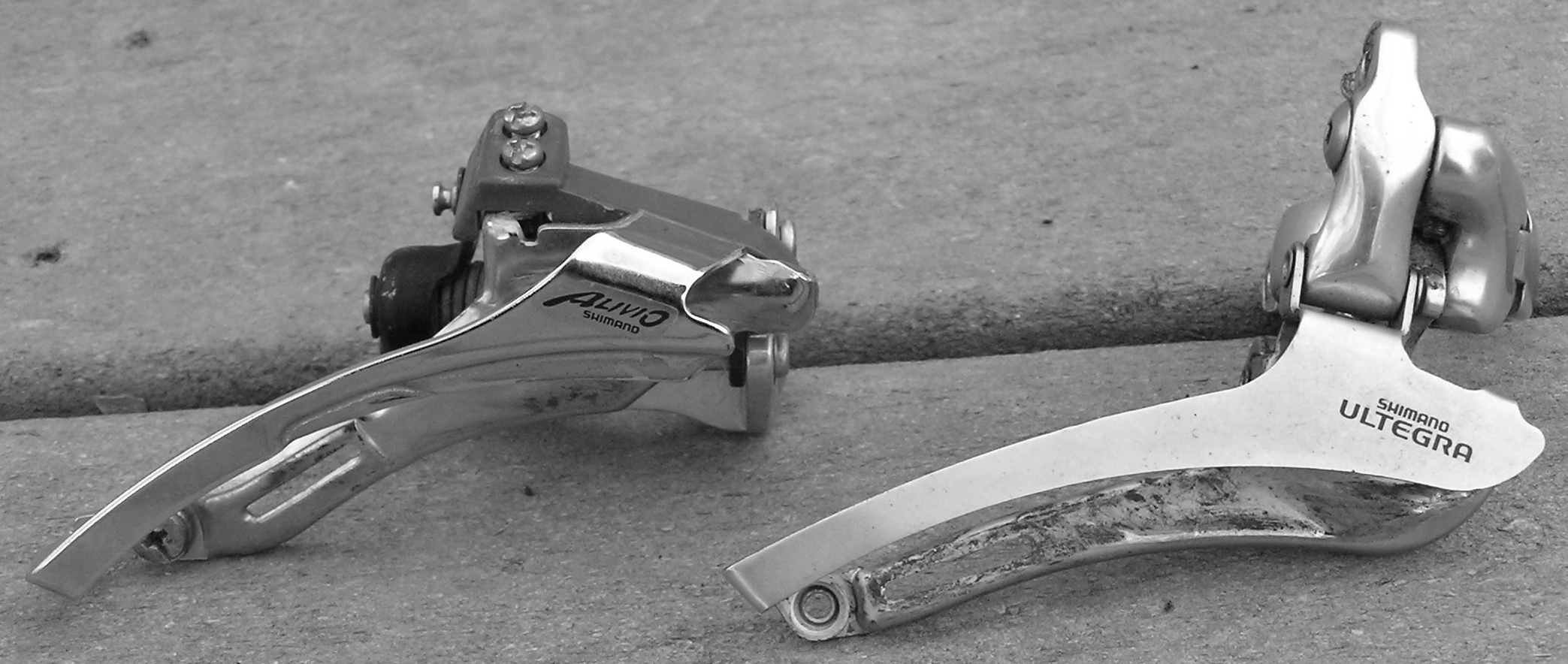 Figure 3: Two front derailleurs. The derailleur on the left has a clamp lower than the top of the cage.