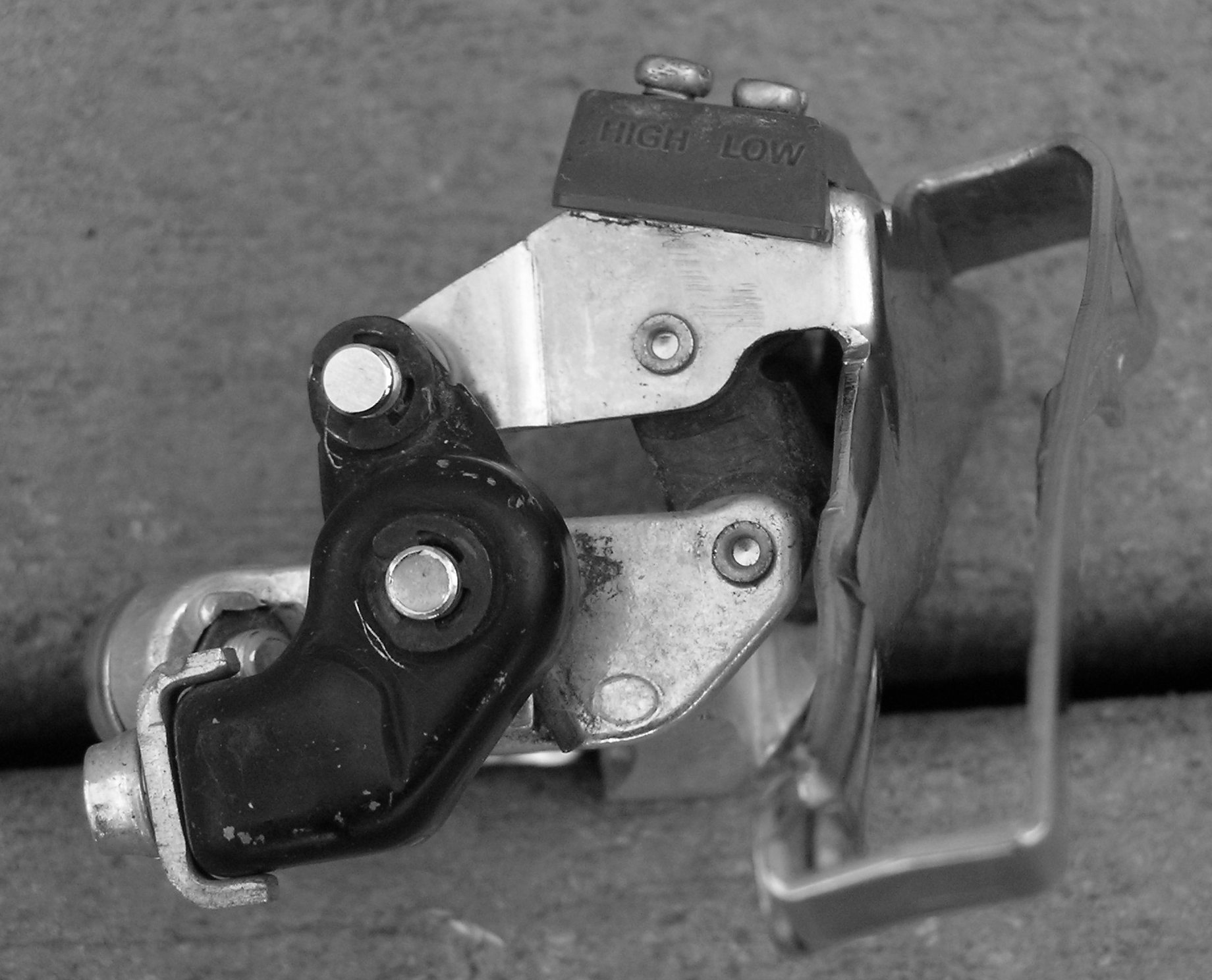 Figure 2: View of a front derailleur from behind. The cage is to the right, the clamp is to the left, and the parallelogram linkage system is in the middle. The lever arm is colored black. The adjustm  ent screws are up top.